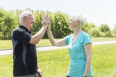 Senior couple running in park doing high five royalty free stock photo