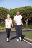 Senior Couple Running On Road Stock Image
