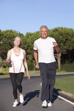 Senior Couple Running On Road Royalty Free Stock Image