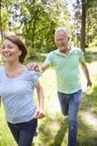 Senior Couple Running In Summer Countryside stock image
