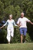 Senior Couple Running Through Summer Field Stock Images