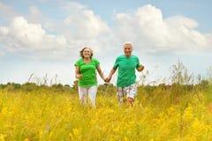 Senior couple running in summer field Royalty Free Stock Image