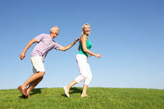 Senior couple running though field. In the sun Stock Photos