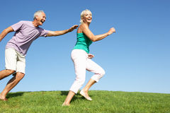 Senior couple running though field. In the sun Stock Images