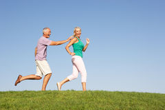 Senior couple running though field. In the sun Stock Photo