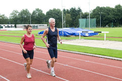 Senior Couple Running On A Track. Senior couple running together on a track in a stadium Royalty Free Stock Images