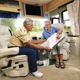 Senior couple in RV. Senior couple sitting in RV looking at map and smiling Stock Photography