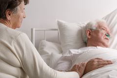 Senior couple`s last moments. Senior loving couple`s hearthbreaking touching last moments in hospice stock photos