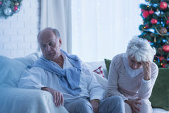 Senior couple sad at Christmas. Lonely and sad senior couple sitting on a sofa at Christmas time Royalty Free Stock Photo