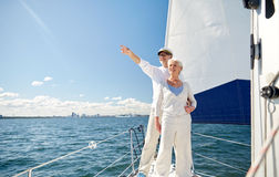 Senior couple sailing on boat or yacht in sea. Sailing, age, tourism, travel and people concept - happy senior couple pointing finger to something on sail boat stock photos