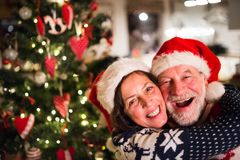 Senior couple with Santa hats at Christmas time. Beautiful senior couple in woolen sweaters with nordinc pattern at Christmas time, hugging. Man and women Royalty Free Stock Images