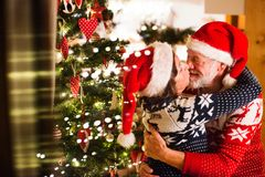 Senior couple with Santa hats at Christmas time. Beautiful senior couple in woolen sweaters with nordinc pattern at Christmas time, kissing. Man and women Stock Photography