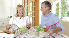 Senior couple seated around dining  stock video