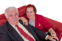 Senior couple seated on a red couch Stock Images