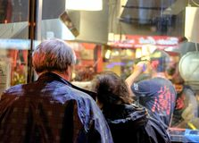 Senior couple seen looking at a restaurant menu in a window. stock photography