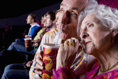 Senior couple sharing drink in cinema, close-up royalty free stock photos