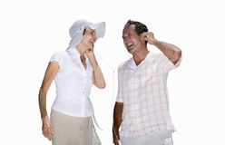 Senior couple sharing headphones, smiling, side view, cut out Stock Images