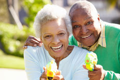 Senior Couple Shooting Water Pistols Stock Photo