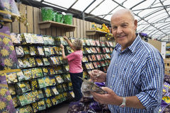 Senior couple shopping in garden centre, man holding flower bulbs, smiling, side view, portrait Royalty Free Stock Image