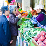 Senior couple shops for vegetables at an outdoor m Stock Photo