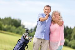 Senior couple showing OK sign on a golf course. royalty free stock photography