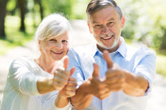 Senior couple showing thumbs up. Loving senior couple standing outdoors Stock Image
