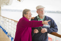 Senior Couple Sight Seeing on The Deck of a Cruise Ship. Happy Senior Couple Enjoying The View From Deck of a Luxury Passenger Cruise Ship Royalty Free Stock Image