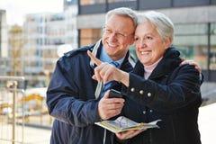 Senior couple on sightseeing tour. Happy senior couple doing sightseeing tour on city trip with a map Stock Photos