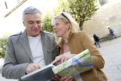 Senior couple sightseeing town with map and tablet Royalty Free Stock Images
