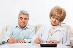 Senior couple sign up document sitting sofa Stock Photos