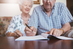 Senior couple signing their will documents. Senior couple signing will documents. Elderly caucasian men and women sitting at home and signing some paperwork Royalty Free Stock Photo