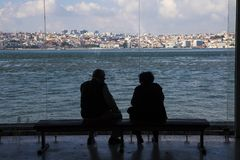 Senior Couple silhouetted against the city of Lisbon Portugal. Senior OAPS waiting for the ferry on a sunny day to transport them Portugal`s capital city Lisbon Royalty Free Stock Image