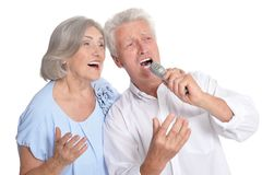 Senior couple singing karaoke isolated. On white background Stock Image