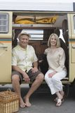 Senior Couple Sit In Campervan With Their Pet Dog. Full length portrait of a happy senior couple sitting with their pet dog in campervan royalty free stock photography