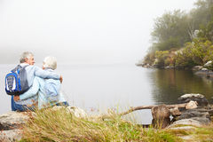 Senior couple sit embracing by a lake, back view Stock Image