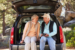 Senior couple sit in open car trunk before a hike, close-up Stock Image