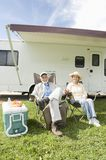 Senior Couple Sit Outside RV Home. Full length portrait of a senior couple sitting on folding chairs outside RV home Royalty Free Stock Photo