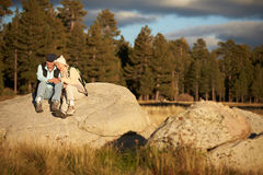 Senior couple sit on a rock near a forest, California, USA Stock Images