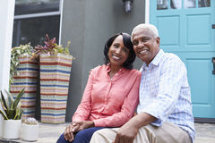 Senior couple sit on steps outside their house, close up royalty free stock photography