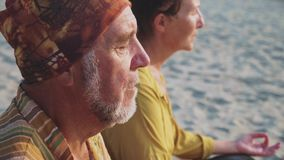 Senior couple sits and meditating together on sandy beach stock video footage