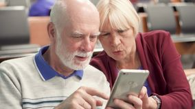 Senior couple sitting in airport terminal waiting for flight using smartphone, browsing, reading news. Senior couple sitting in airport terminal waiting for stock video footage