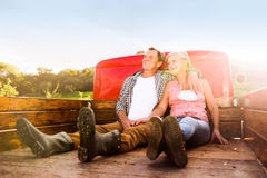 Senior couple sitting in back of red pickup truck Stock Photography