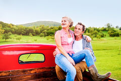 Senior couple sitting in back of red pickup truck Stock Photo