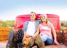 Senior couple sitting in back of red pickup truck Stock Image