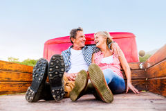Senior couple sitting in back of red pickup truck Royalty Free Stock Images