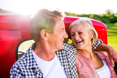 Senior couple sitting in back of red pickup truck Royalty Free Stock Photos