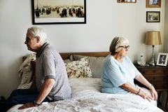 Senior couple sitting back to back Stock Image