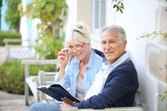 Senior couple sitting in the backyard reading Stock Photo