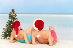 Senior Couple Sitting On Beach With Christmas Tree And Hats. Relaxing Stock Photos