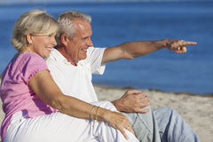 Senior Couple Sitting on Beach Pointing Stock Image